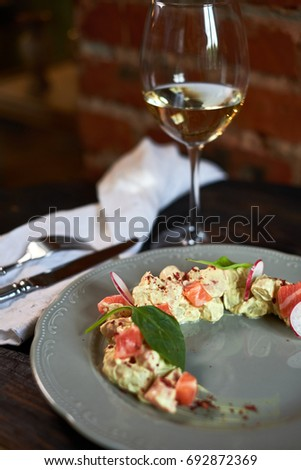 Salad with salmon and radish in the form of a month on a plate