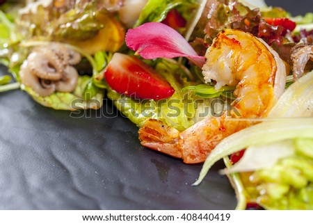 Salad with Shrimp's tails, octopus, squid, mussels and green fresh lettuce  peach strawberry on the white plate