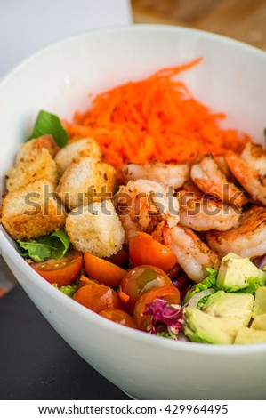 Salad with shrimps, octopus, mussels and calamari with avocado, lettuce, lemon and pineapple in a bowl, napkin on the background light wooden boards