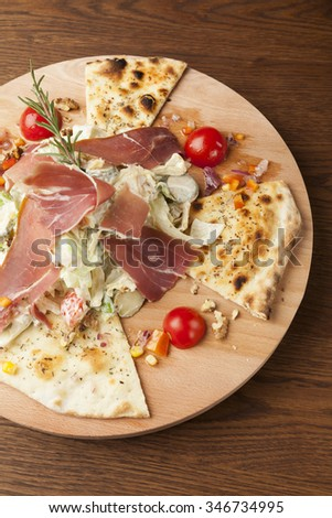 salad with smoked ham and garlic bread on wooden table