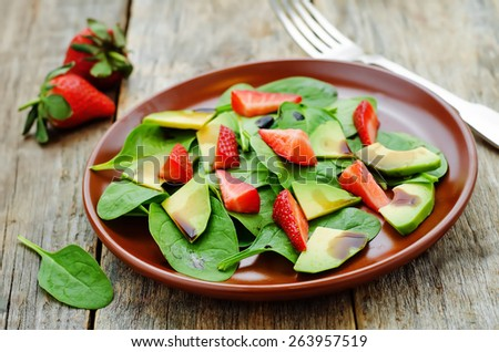 salad with spinach, avocado and strawberries on a dark wood background. tinting. selective focus - stock photo