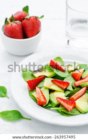 salad with spinach, avocado and strawberries on a white background. tinting. selective focus - stock photo