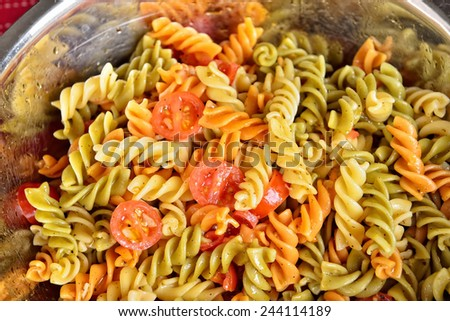 Salad with three colors pasta, cherry tomatoes, garlic, oil and spices in metal bowl - stock photo