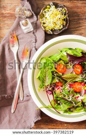 salad with tomato and radish sprouts for dinner on a wooden background - stock photo