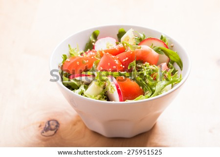 Salad with tomato, cucumber, radish, arugula and sesame seeds with olive oil - stock photo