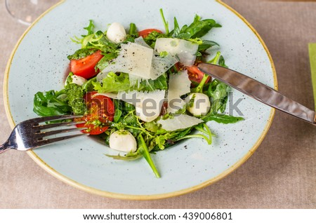 Salad with tomatoes and cheese - mozzarella and parmesan . Close-up on a wooden table.