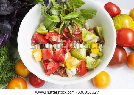 Salad with tomatoes and greens on the table - stock photo