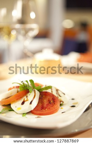 Salad with tomatoes and mozzarella , in the background a restaurant out of focus - stock photo