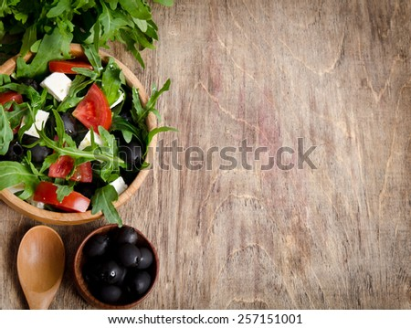 Salad with tomatoes and olives on wooden background.bunch arugula, a bowl of olives, a bowl of salad and a wooden spoon with one hand with the other place for your text - stock photo