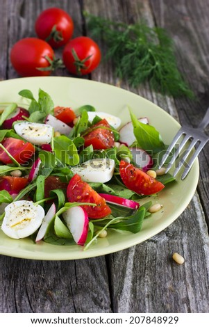 salad with tomatoes, eggs, arugula and radish