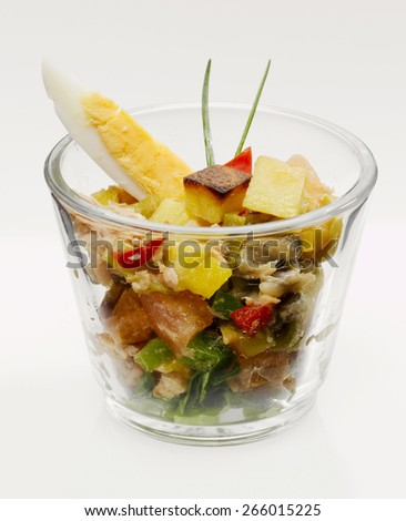 Salad with tuna, anchovies and vegetable in glass, close-up - stock photo