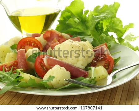 Salad with vegetables and ham and olive oil