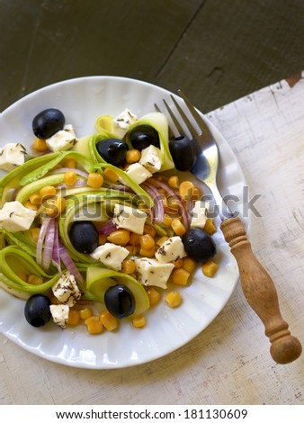 Salad with zucchini, olives, corn and marinated cheese with selective focus