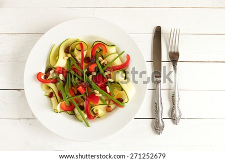 Salad with zucchini, paprika, chive and dried fruits - stock photo