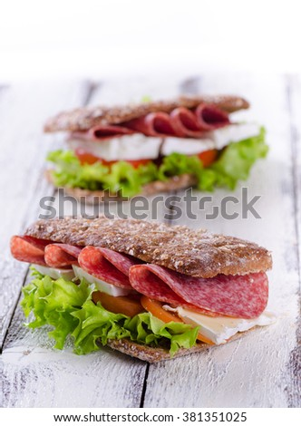 Salami and brie sandwich with whole wheat bread on white wooden background