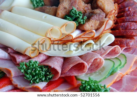 Salami and cheese rolls with vegetables - stock photo