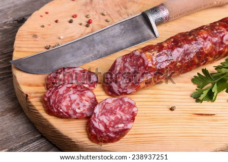 Salami and knife on a cutting board, top view - stock photo