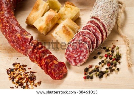 Salami and spicy salami with focaccia pizza decorated with  peppergrain and grounded red pepper over a wooden chunk-board - stock photo