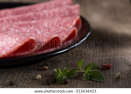 Salami on black plate over wooden rustic background - stock photo