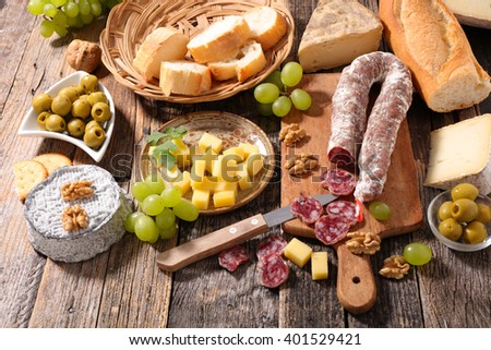 salami on board with cheese and bread - stock photo