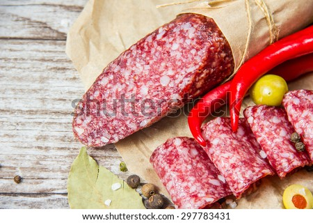 Salami on wooden background with spices - stock photo