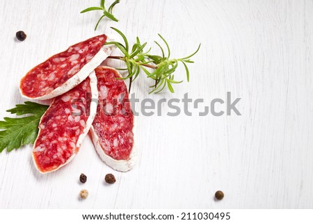 Salami on wooden board with rosemary - stock photo