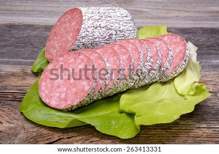 Salami on wooden table - stock photo