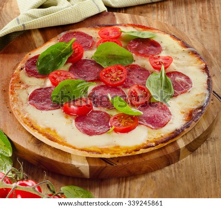 Salami Pizza served on a rustic wooden table. Selective focus