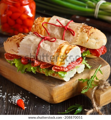Salami sandwiches with lettuce and sweety drop peppers on an old wooden board. - stock photo