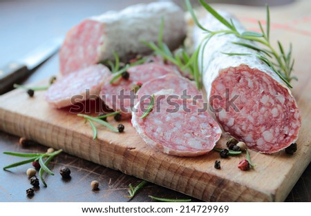 Salami sausage on a wooden cutting board with herbs - stock photo