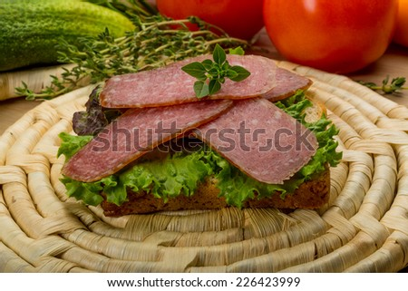 Salami sausages sliced with basil and bread