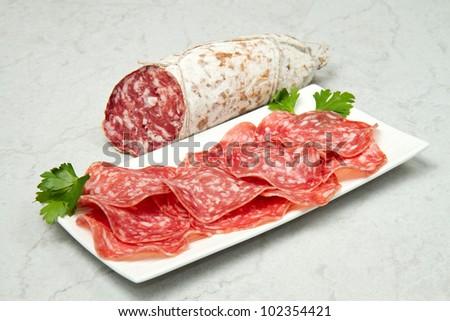 Salami sliced on marble table - stock photo
