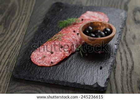 Salami slices slate board, rustic style food - stock photo