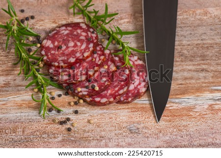 salami slices with pepper, black sharp knife and rosemary on wooden background - stock photo