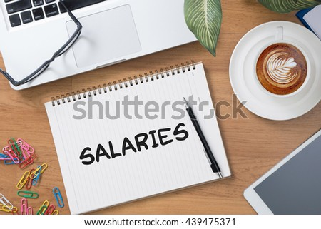 SALARIES Tablet with blank black screen and coffee cup - stock photo