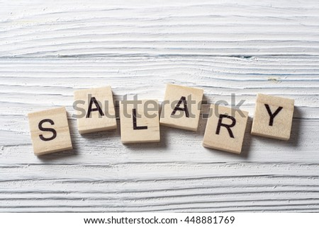 SALARY word written on wood block at wooden background - stock photo