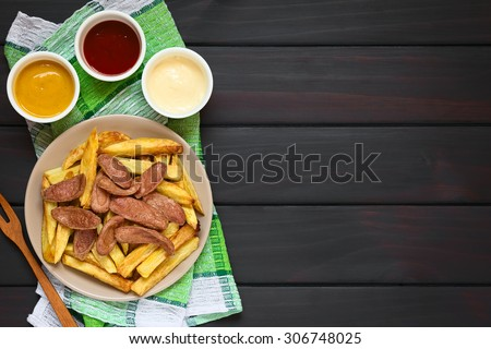 Salchipapas made of French fries and fried sausage, a traditional fast food in South America, mayonnaise, ketchup, mustard above, photographed overhead on dark wood with natural light - stock photo