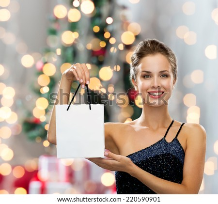 sale, advertisement, holydays and people concept - smiling woman with white blank shopping bag over christmas tree and lights background - stock photo