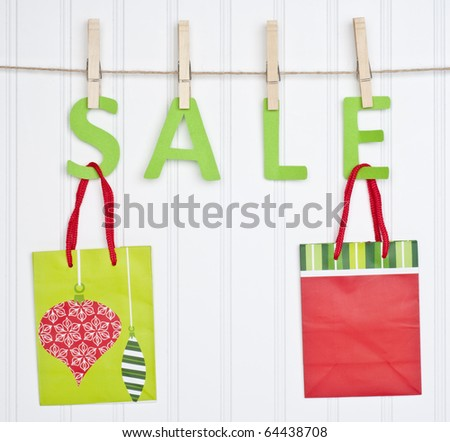 SALE and Holiday Gift Bags on a Clothesline.  Holiday Concept. - stock photo