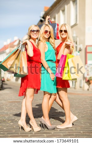 sale and tourism, happy people concept - beautiful blonde women with shopping bags in the ctiy - stock photo