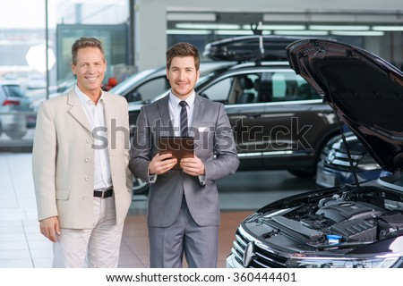 Sale assistant showing the car