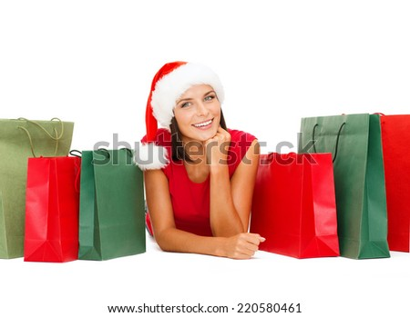 sale, christmas, x-mas concept - smiling woman in red shirt and santa helper hat with shopping bags - stock photo