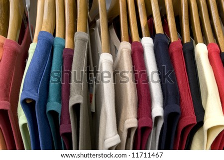 Sale. Clothes lined up in store. - stock photo