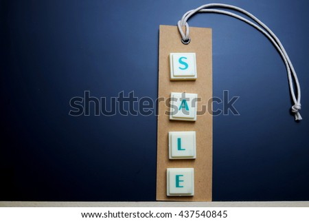 Sale concept. The words spelled by letters with sale tag, brown label on blackboard. Space for texts. Dark tone. - stock photo