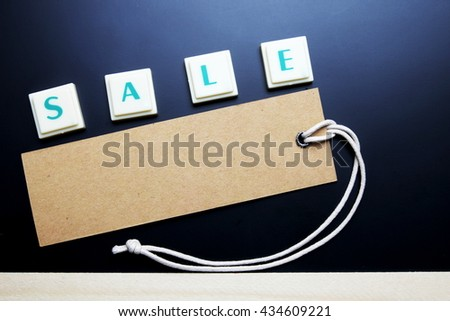 Sale concept. The words spelled by letters with sale tag, brown label on blackboard with wooden border. Space for texts. Dark tone. - stock photo