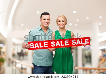 sale, consumerism, advertisement and people concept - happy young couple holding red advertising board in mall - stock photo