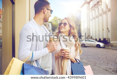 sale, consumerism and people concept - happy couple with shopping bags and coffee paper cups at shop window in city - stock photo