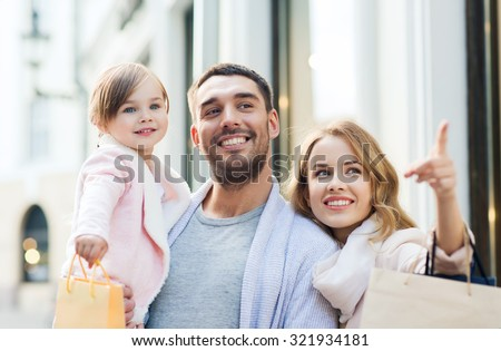 sale, consumerism and people concept - happy family with little child and shopping bags in city - stock photo