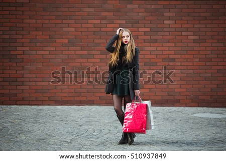 Sale, consumerism and people concept - happy young beautiful women holding shopping bags, walking away from shop.