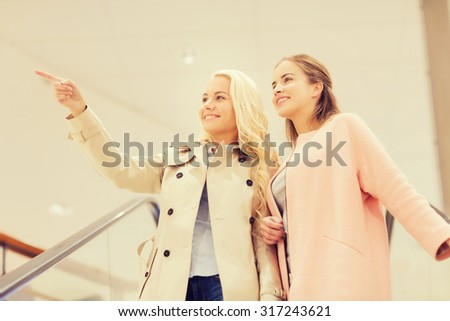 sale, consumerism and people concept - happy young women pointing finger on escalator in mall - stock photo